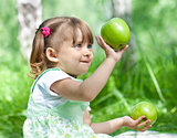 Little girl portrait with 2 green apples in her hands outdoor