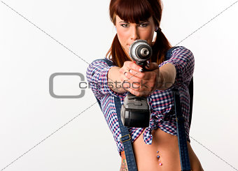 Beautiful Brunette points a cordless drill pausing to play