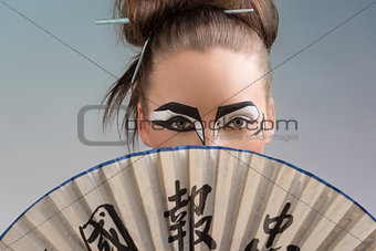 pretty brunette in japan style with fan on the face