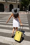 woman back stand on crosswalk with suitcase