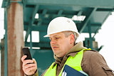 Engineer with cell phone on a transformer background