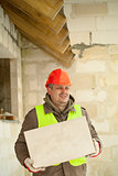 Builder with concrete block near new building