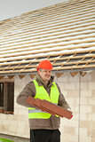 Builder with roof tiles near new building