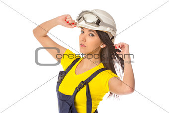 Serious female construction worker in helmet with goggles