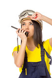 Serious female construction worker talking with a walkie talkie 