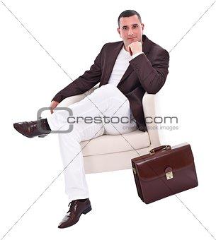 Handsome businessman sitting in armchair