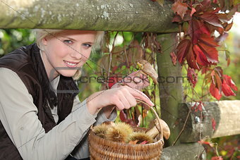 Woman with basket of chestnuts and mushrooms