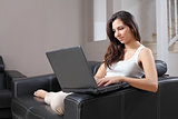 Beautiful woman with a laptop on a couch at home