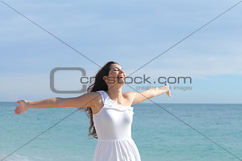 Happy beautiful girl with her arms raised on the beach
