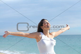 Beautiful girl with her arms raised on the beach