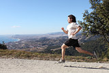 Man running on a path with a big city in the background