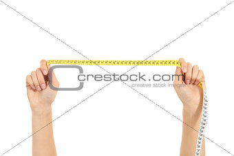 Beautiful woman hands stretching a measure tape