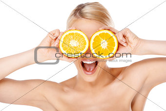 Blond woman making glasses with orange halfs