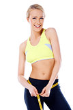 Beautiful smiling blond sporty woman measuring her waist