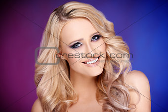 Blond woman with curly hair posing on colorful background