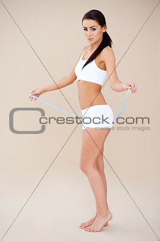 Attractive brunette posing with measure tape