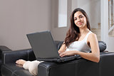 Beautiful woman at home typing in a laptop 