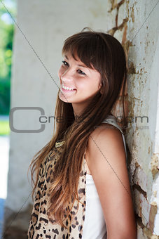 Beautiful smiling woman near the old wall