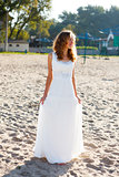 Young smiling woman bride in a white dress on the sunny beach