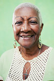 Portrait of senior black woman smiling at camera on green backgr