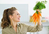 Happy young housewife holding carrots in kitchen