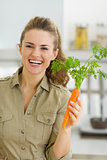 Happy young housewife holding carrot in kitchen