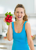 Smiling young woman holding bunch of radishes in kitchen