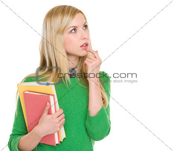 Portrait of thoughtful student girl looking on copy space
