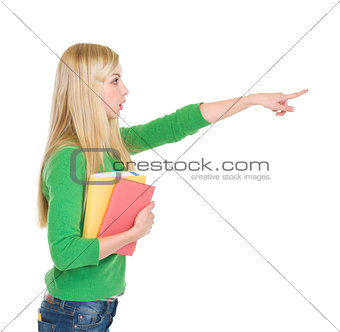 Surprised student girl pointing on copy space