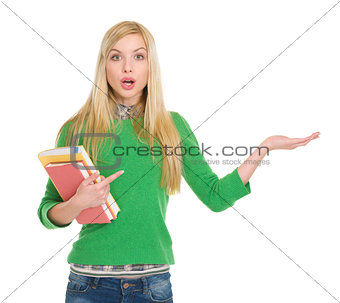 Surprised student girl pointing on empty hand