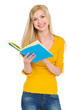Smiling student girl reading book