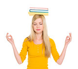 Student girl with books on head meditating