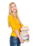 Smiling student girl holding stack of books
