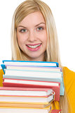 Happy student girl holding stack of books