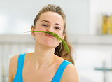 Funny young woman using dill as mustache in kitchen