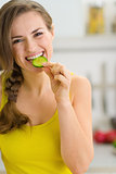 Smiling young woman eating slice of cucumber