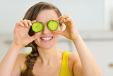 Smiling young woman holding slices of cucumber in front of eyes