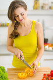 Young woman cutting yellow bell pepper on cutting board