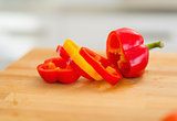 Closeup on red bell pepper with yellow slice on cutting board