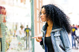 Black woman, afro hairstyle, looking at the shop window 