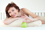 attractive young woman with an green apple at bed