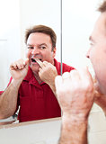Flossing Teeth In Bathroom Mirror