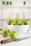 Green apples in bowl on table