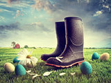 Rubber boots with easter eggs on grass