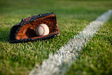 Baseball mitt and ball in grass by field stripe