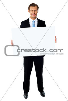 Portrait of businessman showing blank signboard