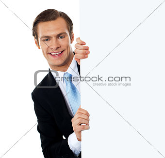 Smiling business professional behind blank clipboard