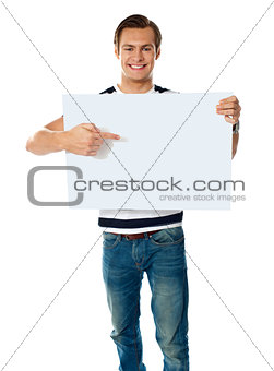 Portrait of young man pointing at blank signboard