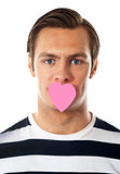 Good looking guy with heart shaped paper on his mouth
