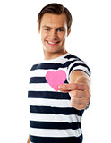 Young man ofering his paper heart to you